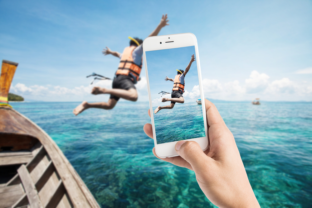 Man using photography app to take a picture of a man jumping out of a boat into the ocean