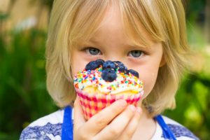 Child holding a sugar frosted cupcake