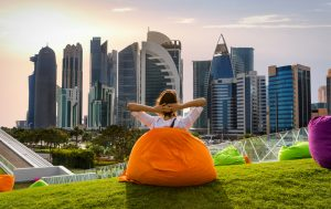 Woman sitting on a bean bag in a park and watching the skyline in Doha