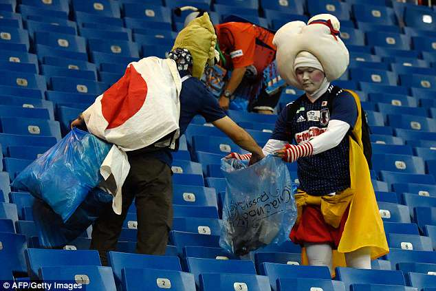 Japanese fans cleaning the stands after the match